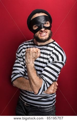 Portrait of a angry bandit threaten with a fist