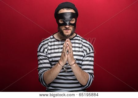 Angry burglar with handcuffs