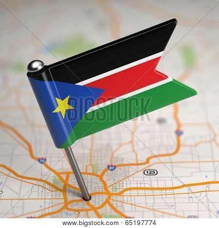 South Sudan Small Flag on a Map Background.