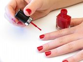 picture of nail paint  - woman painting her nails with red polish over white background - JPG