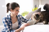 pic of caress  - Smiling woman with tablet and beautiful cat in the living room.