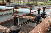 pic of valves  - Rusty big tap valve gate and pipes in water treatment plant and dirty liquid bubble in background - JPG