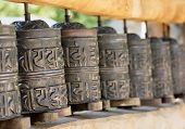 stock photo of sanskrit  - A prayer wheel is a cylindrical wheel on a spindle made from metal wood stone leather or coarse cotton - JPG