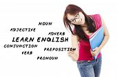 stock photo of nouns  - Female student writes English language materials on whiteboard - JPG