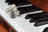 stock photo of stare  - One hundred dollar bill stuck in a piano - JPG