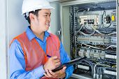 image of breaker  - Asian Indonesian Technician or electrician making function test on breaker box or switchbox with power lines on construction site or in factory for acceptance - JPG