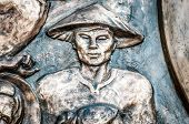 picture of metal sculpture  - Part of bronze monument with asian man in traditional conical hat - JPG