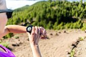 pic of canary  - Trail runner or hiker on mountain path looking at sportwatch checking performance or heart pulse - JPG