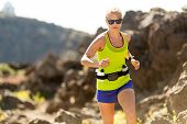 foto of canary-islands  - Young woman running in mountains on sunny summer day - JPG