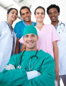 stock photo of health-care  - International medical team with a confident surgeon with folded arms in the foreground - JPG