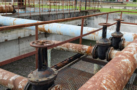 picture of groundwater  - Rusty big tap valve gate and pipes in water treatment plant and dirty liquid bubble in background - JPG