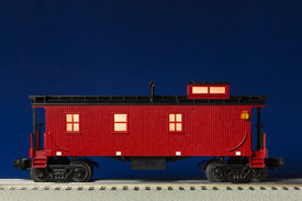 picture of caboose  - A red railroad caboose illuminated on track - JPG