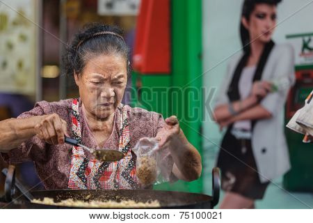 BANGKOK, THAILAND, DECEMBER 10, 2012: An elderly woman street food seller is filling a plastic bag for a customer in Chinatown, Bangkok, Thailand