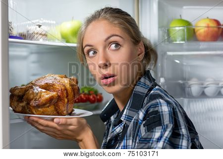 Girl holding fried chicken near opened refrigerator