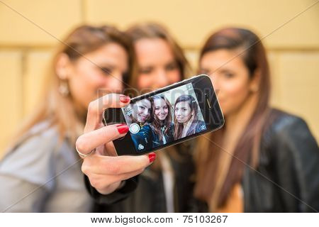 Friends taking a self portrait with smart phone