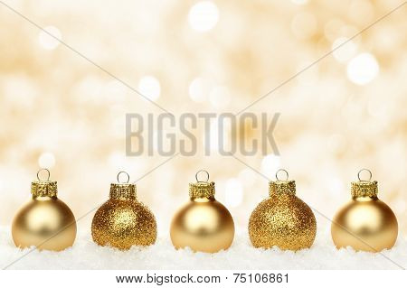 Gold Christmas background with baubles in snow