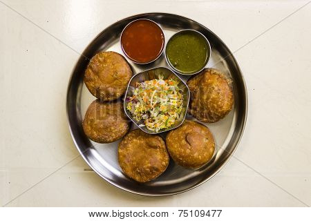 Indian snack called Kachori served with sweet & sour ketchup, spicy chilly chutney and salad