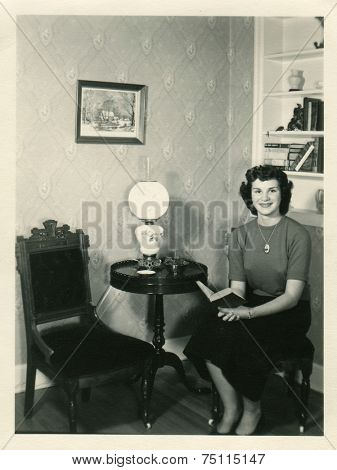 CANADA - CIRCA 1940s: Vintage photo shows young girl in the interior of her room.