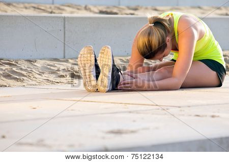 Young, very flexible woman in sportswear, touching her knees with her nose. She's stretching her muscles during a training run on the beach boulevard on a sunny summer evening.
