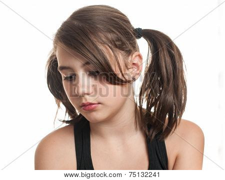Beautiful teen girl with two pigtails in black top having a sad expression on her face