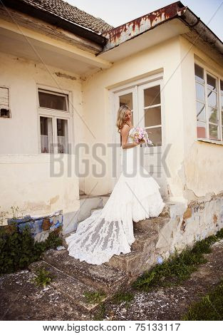 Blonde bride with veil by old house