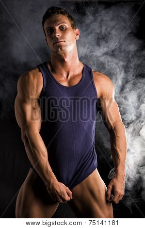 Young Athletic Man Pulling Down Tanktop On Ripped Muscular Torso