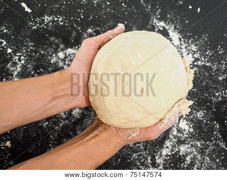 Person Holding A Proven Dough Over Black Table With Flour Mess