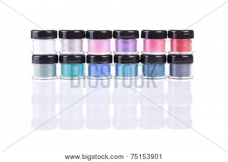 Two rows of loose eye shadows in plastic jars, isolated on white background with natural reflection