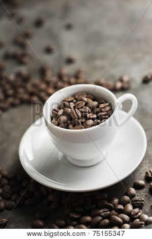 Roasted coffee beans with coffee cup
