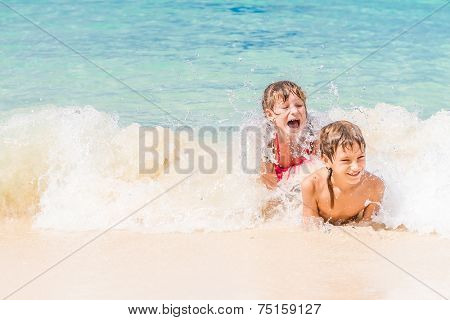 two young happy children - girl and boy - having fun in water, tropical summer vacations, holidays