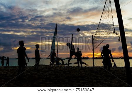 beach volleyball, sunset picture, silhouettes of players on sea background