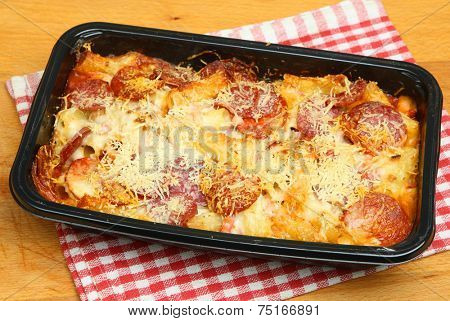 Pasta ready meal with salami sausage, ham and cheese.