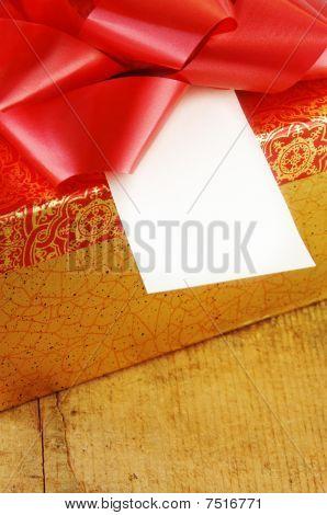 Presente con el lazo rojo y tarjeta de regalo en blanco