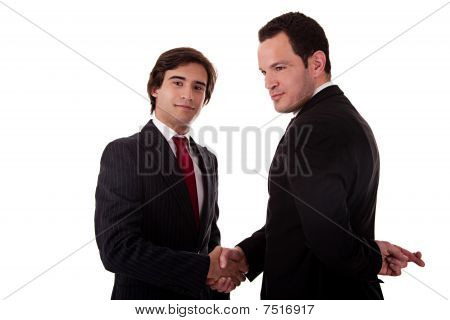 Two Businessmen Shaking Hands, And One Businessman With His Fingers Crossed Behind His Back And Smil