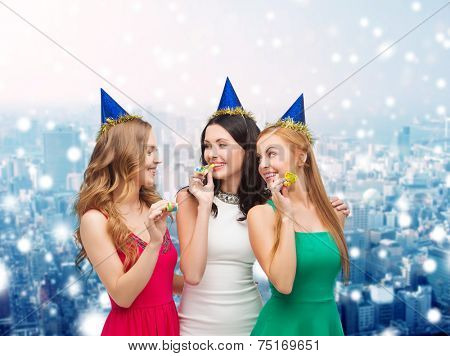 holidays, people and celebration concept - smiling women in party caps blowing to whistles over snowy city background