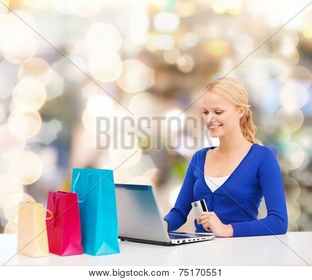 christmas, holidays, technology and shopping concept - smiling woman with shopping bags, credit card and laptop computer over lights background