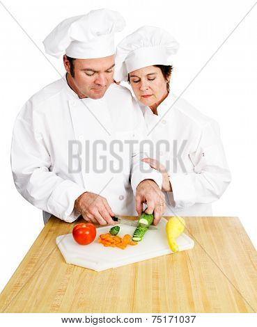 Female chef watches her male student chop vegetables on a cutting board in cooking class.  Both are in full chef's whites.  Isolated on white background.