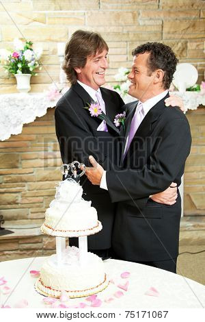 Two handsome gay men in tuxedos embrace with love at their wedding reception.  Wedding cake and rose petals in foreground.