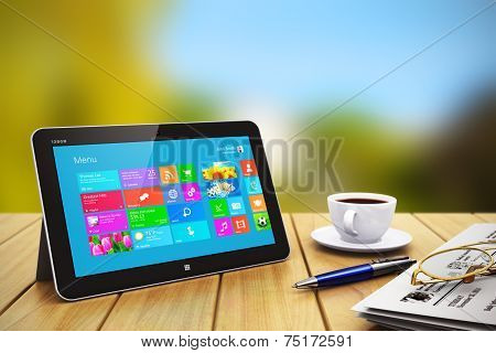 Tablet computer with business objects on wooden table outdoors