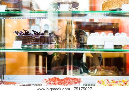Woman selecting a cake from the pastry shop glass display