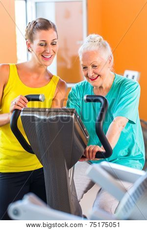 Senior woman with trainer in fitness club exercising on stationary bike for a workout
