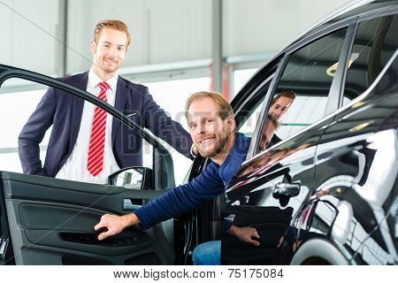 Seller or car salesman and client or customer in car dealership presenting the interior decoration of new and used cars in the showroom