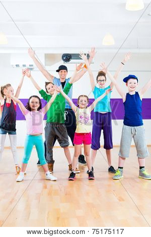 Dance teacher giving children Zumba fitness class in gym