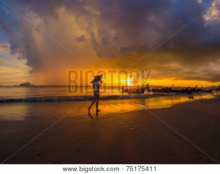 Woman on the beach at  Sunset in Krabi Thailand