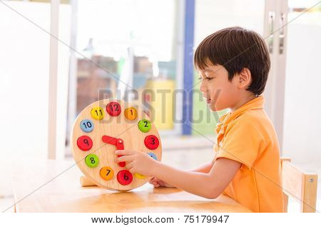 Little Boy Learning Time With Clock Toy Of Montessori Educational Materials