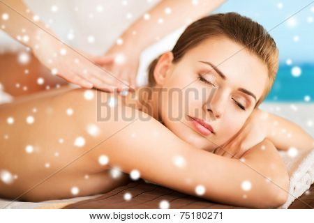 beauty, health, holidays, people and spa concept - beautiful young woman in spa salon getting massage over blue sky and sea background