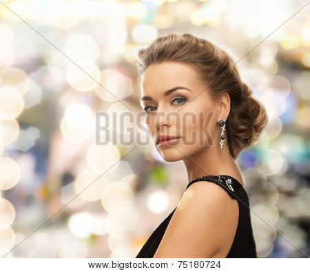 people, holidays, christmas and glamour concept - beautiful woman in evening dress wearing earrings over lights background