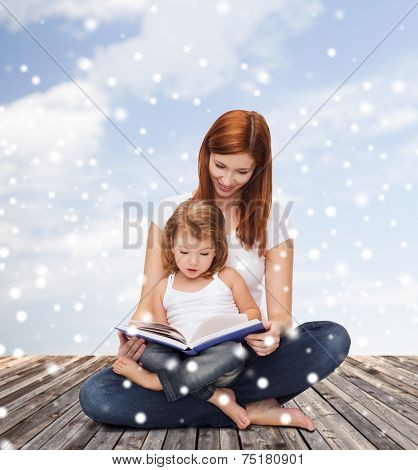 childhood, parenting, people and education concept - happy mother with little girl reading book over wooden floor and blue sky background