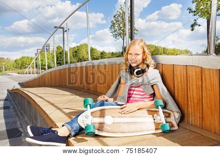 Cute girl holds skateboard wearing headphones