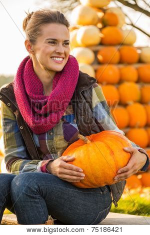 Portrait Of Happy Young Woman Sitting With Pumpkin In Front Of P
